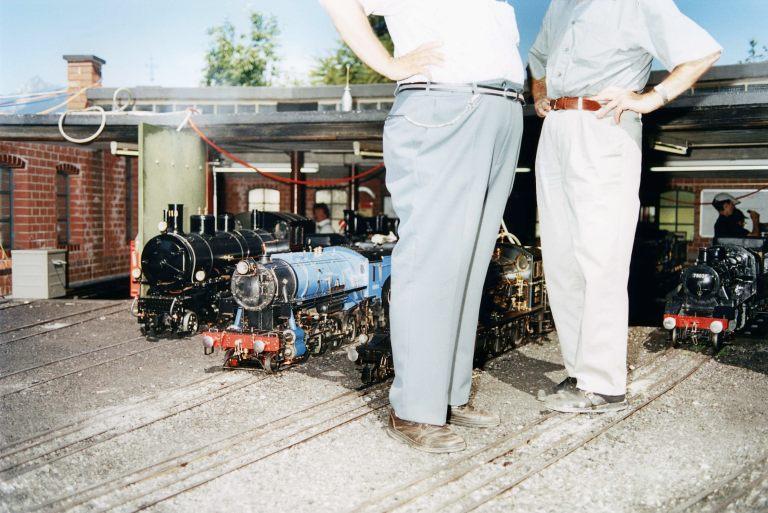 PROJEKT SCHWEIZ - Eisenbahnfans stehen waehrend des Internationalen Dampf-Festivals im Swiss Vapeur Parc in Le Bouveret, Schweiz, zwischen den Miniatur-Dampflokomotiven auf dem Miniaturbahnhof, aufgenommen am 20. Juni 2003. Im Swiss Vapeur Parc befindet sich eine Miniaturbahnstrecke, auf der Dampflokomotiven fahren. (Stefan Jaeggi for KEYSTONE)
