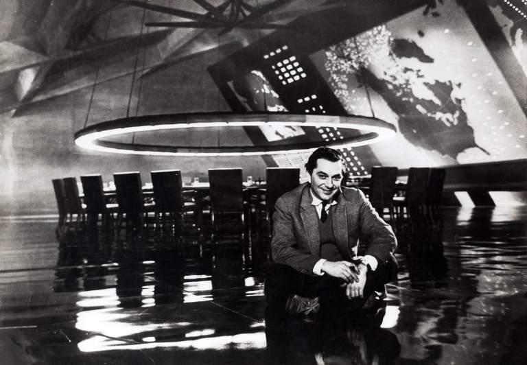 """Ken Adam, 1963 Am Set des """"War Room"""" aus DR. STRANGELOVE OR: HOW I LEARNED TO STOP WORRYING AND LOVE THE BOMB GB/USA 1964, Regie: Stanley Kubrick Quelle: Deutsche Kinemathek – Ken Adam Archiv"""